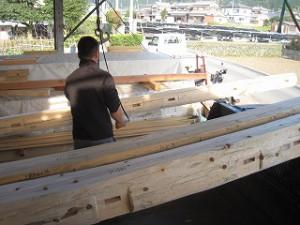 新築工事の建前・上棟で丸太梁の積み込み